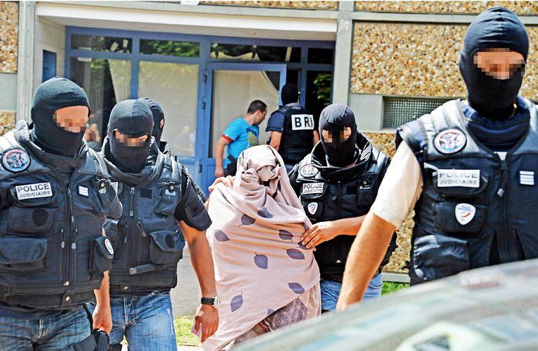 Politie escorteert een verdachte vrouw na een huiszoeking bij Yacine Salhi Beeld epa