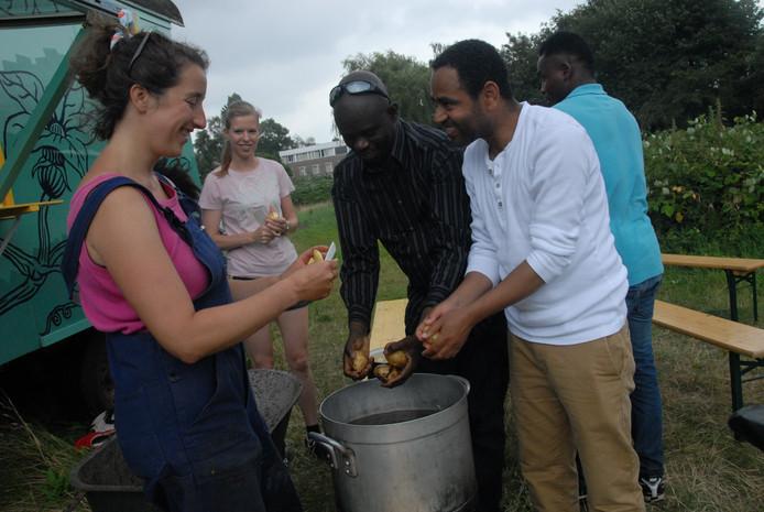 Gezamenlijke bereiding van de maaltijd, links medeorganisator Sophie Gruijters van de stichting Transfarmers.