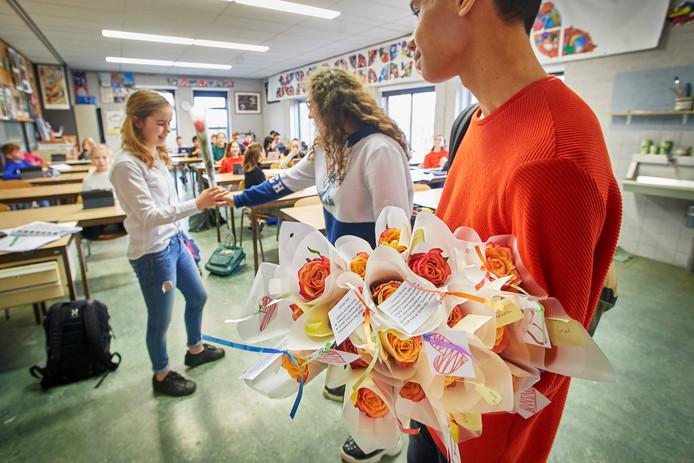 Oliwia (midden) en Fanuel delen rozen uit op het Maaslandcollege.
