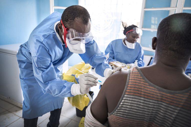 Dokter Al Hassane Touré overgevlogen uit Guinee waar in 2014 een grote Ebola uitbraak te bestrijden was, vaccineert lokaal gezondheidspersoneel met het nieuwe Ebola vaccin. Beeld Sven Torfinn
