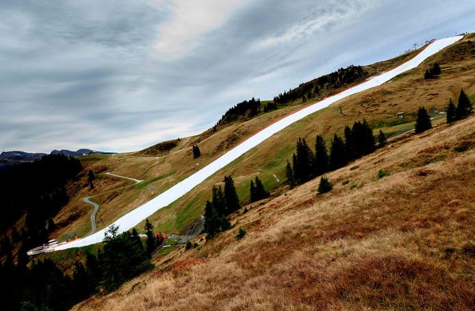 Een witte streep midden in het groene en bruine herfstlandschap van de Oostenrijkse Alpen