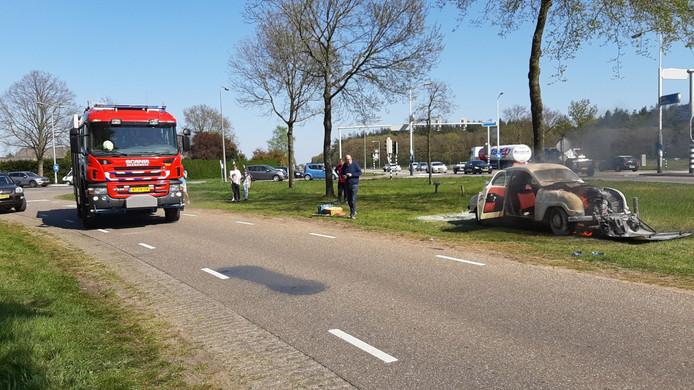 De vlammen slaan uit het motorblok van de auto in Dalfsen.