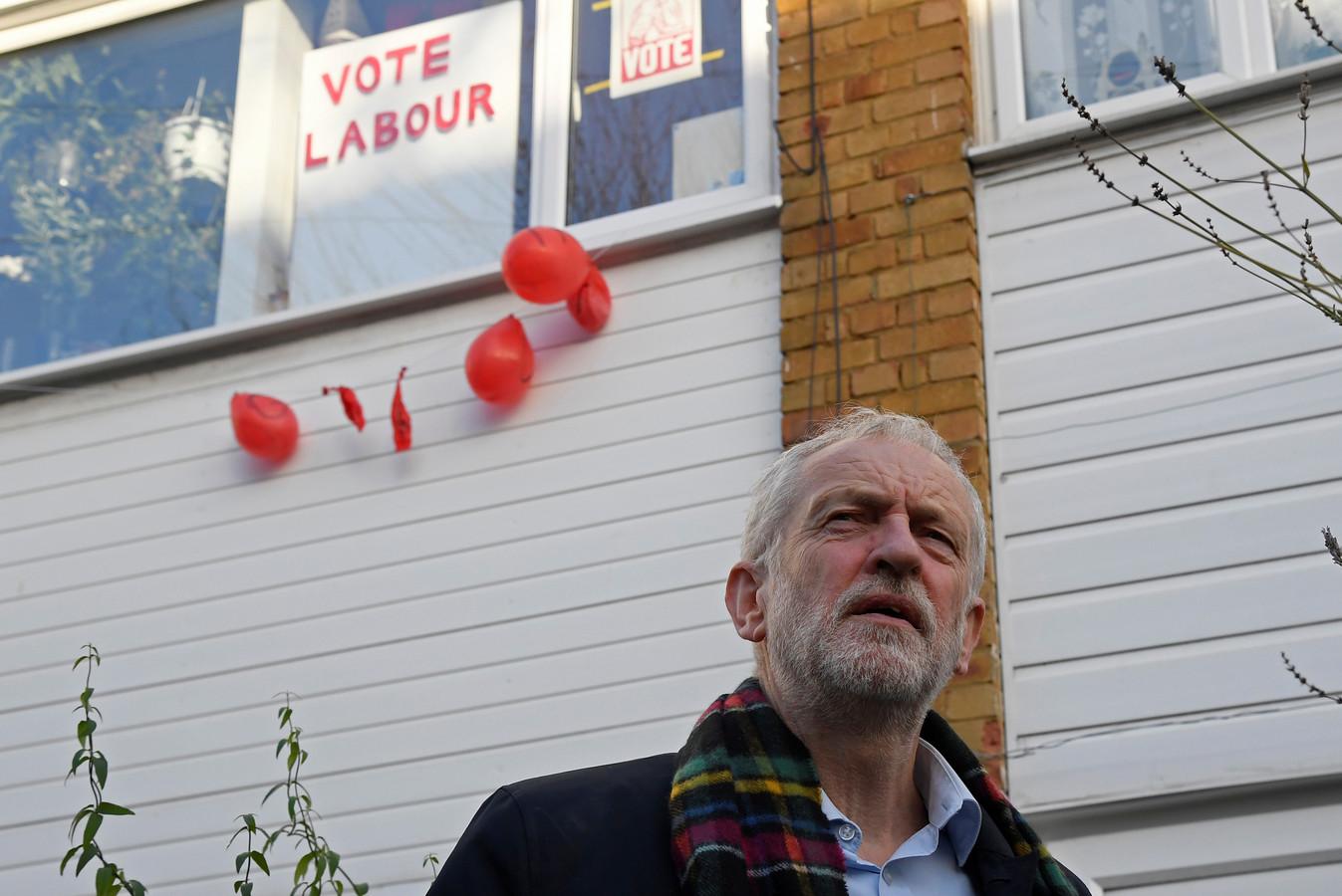 Labour-leider Jeremy Corbyn voor zijn huis in Londen, waar de politieke boodschappen nog volop zichtbaar zijn.