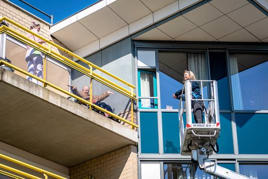 Een dochter wordt met een hoogwerker omhoog getakeld zodat ze door het raam haar moeder even kan zien in een verpleeghuis. Verpleeghuis Rijckehove in Capelle.