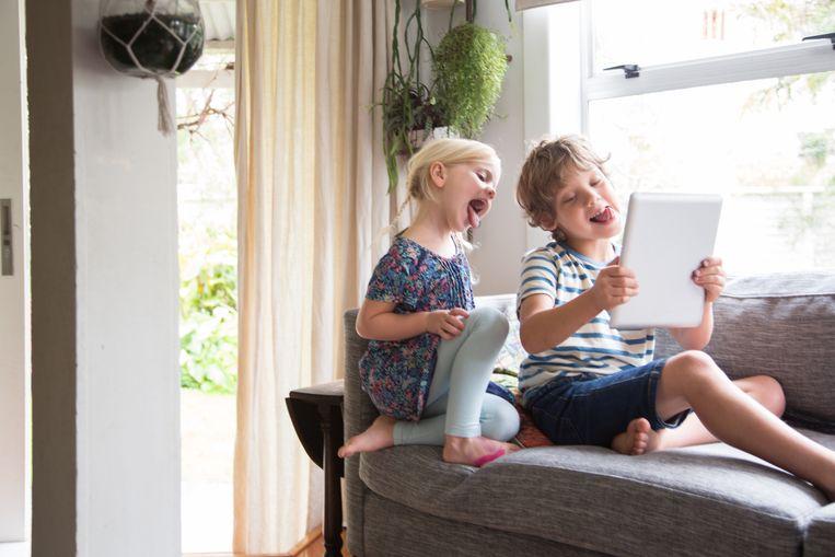 Broer en zus spelen met een tablet.