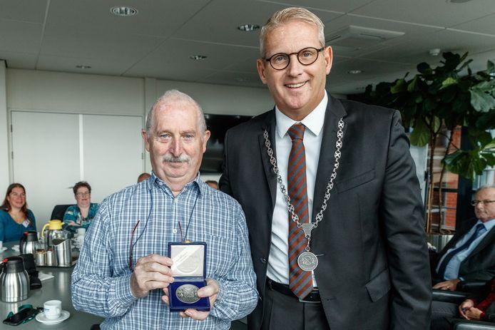 Jan Gorissen (links) toont trots de erepenning die hij net heeft ontvangen van burgemeester Ruud van den Belt.