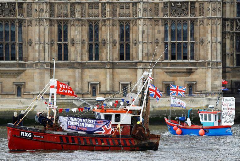 Bootjes met vlaggen met de oproep om uit de EU te stappen varen voor het parlement in Londen langs. Archiefbeeld uit 2016.