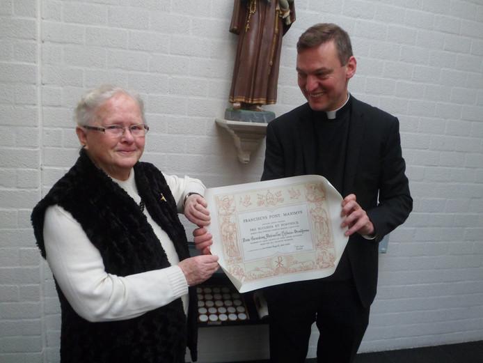 Diny Broekhoven krijgt de pauselijke onderscheiding uit handen van pastoor Harm Schilder.