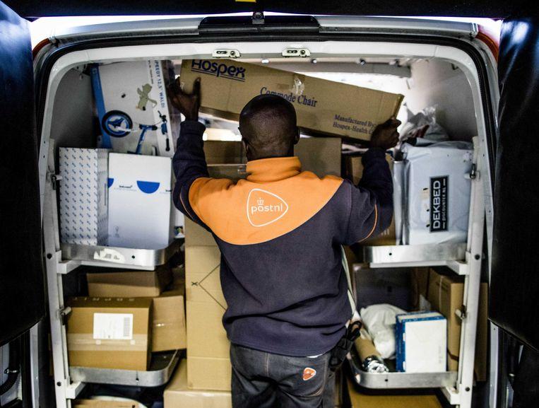 Een pakkettenbezorger van Post NL aan het werk.