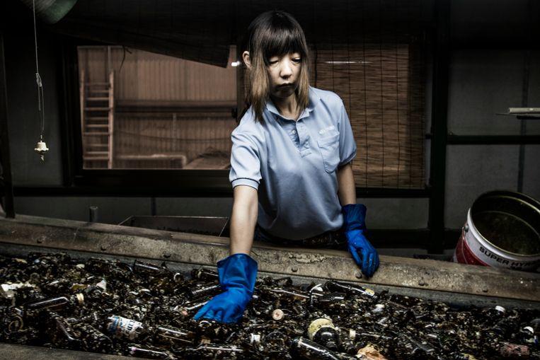 In Ryugasaki, Japan, wordt dagelijks 350 ton glas gerecycled. Kaori Kimchi (48) werkt sinds 2001 in de fabriek. Haar taak is het verwijderen van de rommel tussen de glazen flessen.  Beeld Kadir van Lohuizen