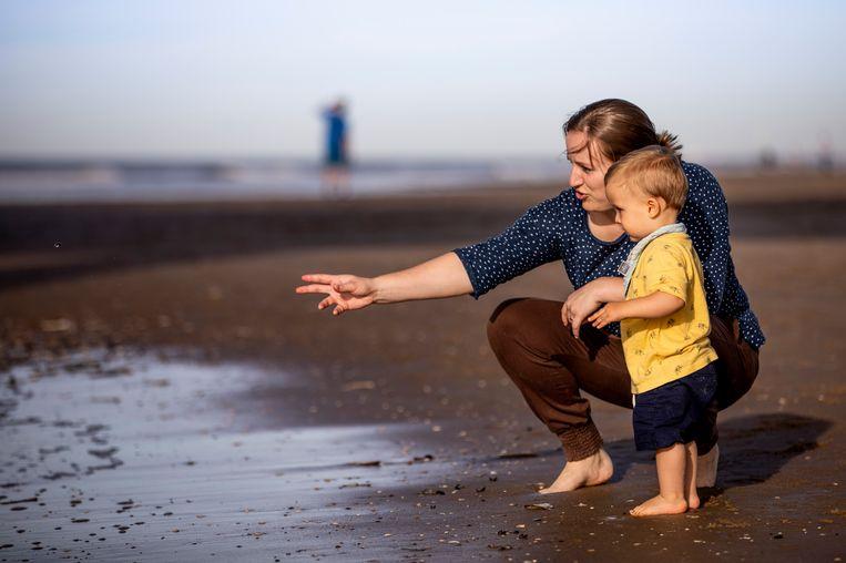 Moeder en kind genieten op het strand in Scheveningen van het warme oktoberweer.  Beeld Freek van den Bergh