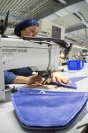 Medewerkers bereiden mondkapjes voor in een naaiatelier van beddenfabrikant Auping. Verschillende Nederlandse bedrijven maken de komende weken mondneusmaskers tegen het coronavirus.