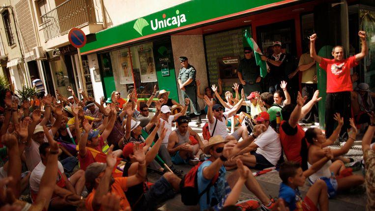 Protest van seizoenswerkers en vakbondsleden voor een filiaal van Unicaja in Mancha Real, op 17 augustus. Beeld REUTERS