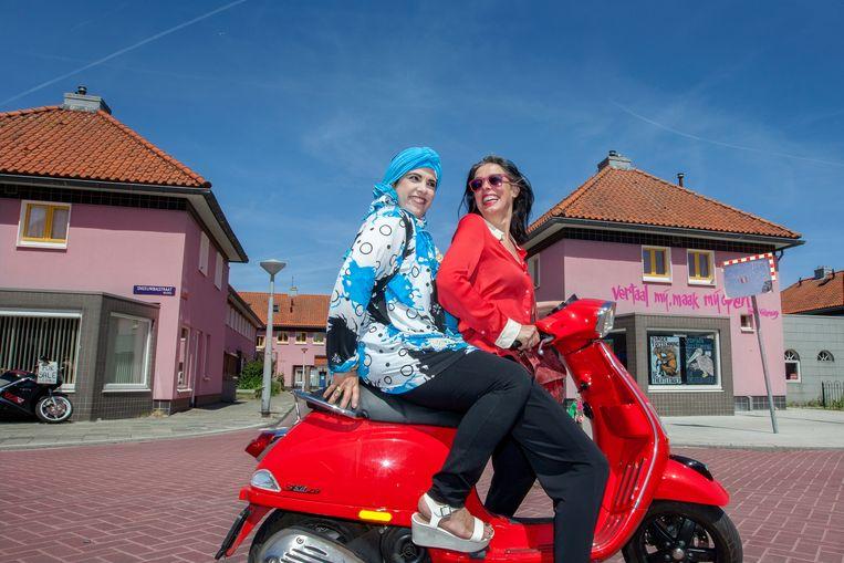 Adelheid Roosen op de scooter in Noord samen met Abier, een wijk-adoptie moeder. Beeld Maartje Geels