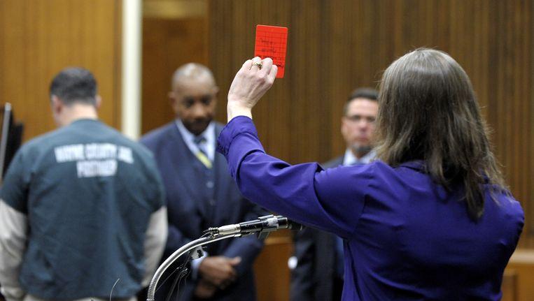 De weduwe van de scheidsrechter houdt in de rechtszaal een rode kaart omhoog. Beeld ap