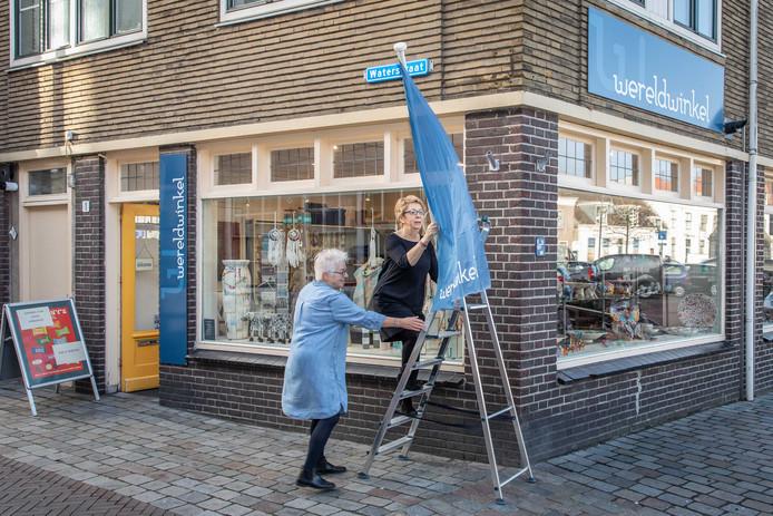 Wereldwinkel-vrijwilligsters Reinhilde van Heijst (op de trap) en Elly Michielsen hangen de vlag buiten.