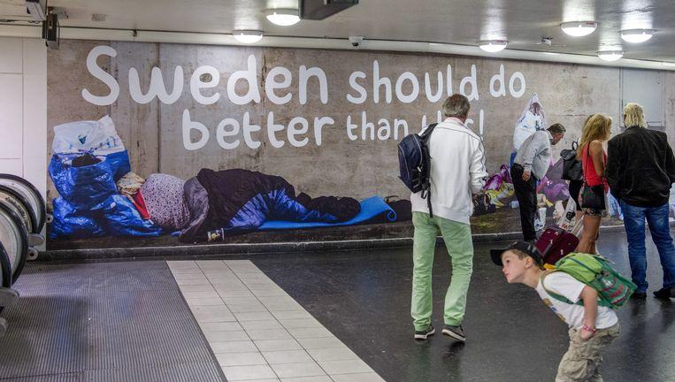 Mensen lopen langs een poster waarop daklozen zijn afgebeeld en de volgende tekst staat: 'Zweden kan beter dan dit'. De poster is een campagne van de Zweden-Democraten. Beeld EPA