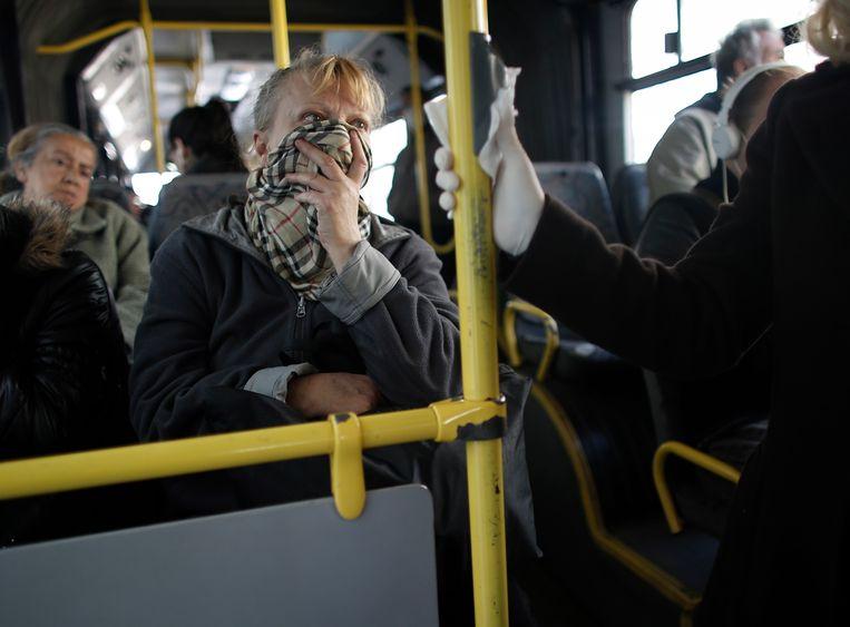 Reizigers op een bus beschermen zichzelf met een sjaal. Volgens viroloog Steven Van Gucht is het veel belangrijker om contact te vermijden en afstand te bewaren.