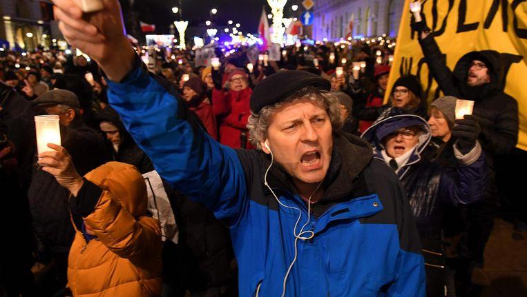 Mensen demonstreren vrijdagavond voor het presidentiële paleis in Warschau. Beeld afp