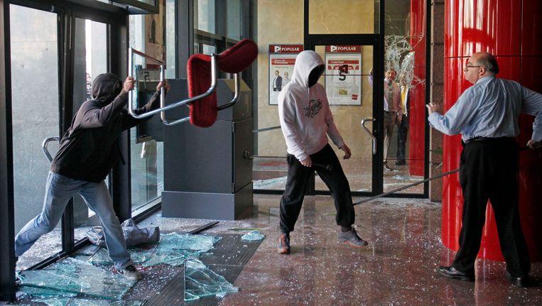 Februari van dit jaar: Spaanse betogers vallen een bank in Barcelona binnen tijdens een demonstratie. Beeld REUTERS