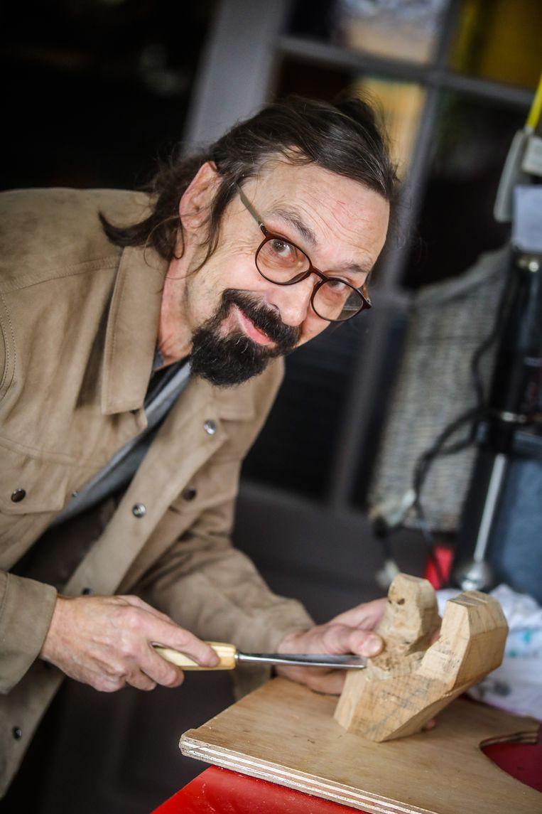 Chris Lowyck is bezig met een tweede hand uit hout. Die zal een visitekaartje vasthouden.