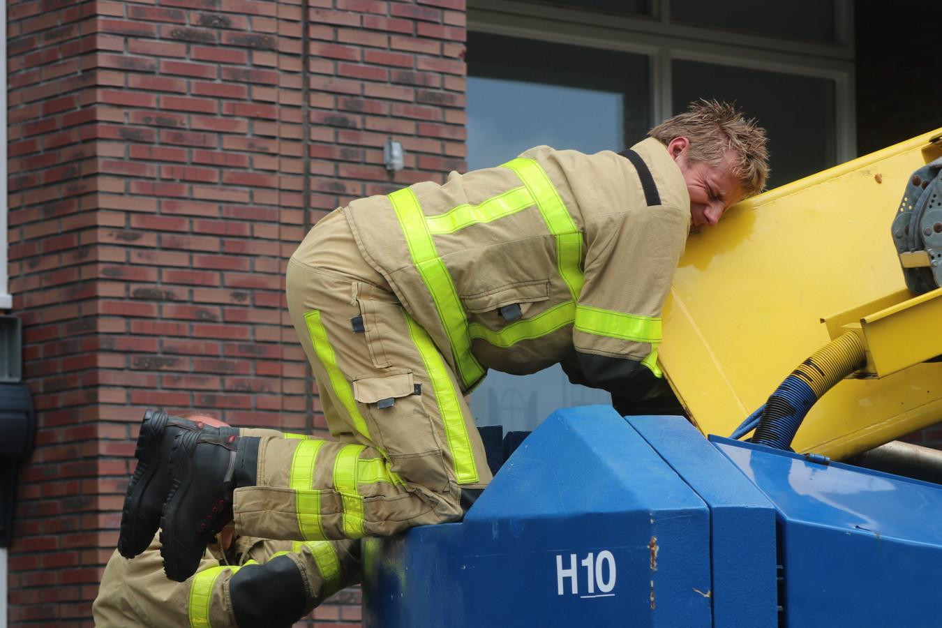 Met een uiterste krachtsinspanning probeert een brandweerman de kat uit de hoogwerker te trekken