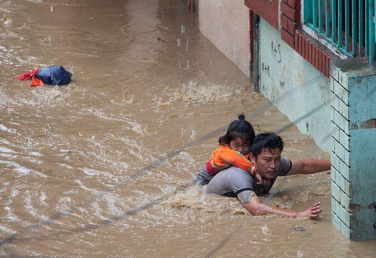 Een man draagt zijn dochter om aan de overstroming te ontkomen in Kathmandu, Nepal. Beeld EPA