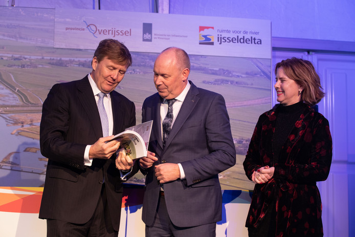 Koning Willem-Alexander bladert door het boek 'Deining in de IJsseldelta', dat is geschreven door de Zwolse auteur Joep Boerboom.