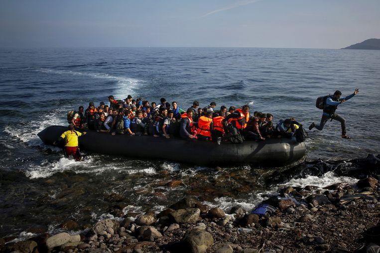 Een migrant springt van de boot op het Griekse eiland Lesbos. Beeld Reuters
