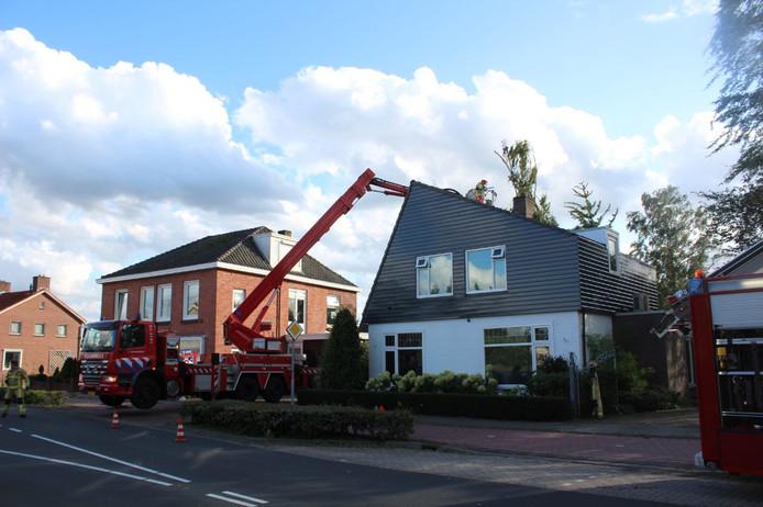 De brandweer maakt gebruik van een hoogwerker om een boom van een dak van een huis in Zenderen te halen.