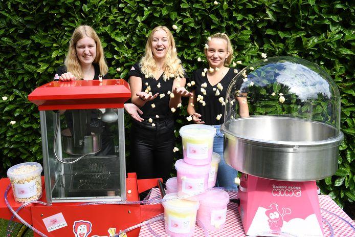 Robin Kostense (m) voor haar popcorn- en suikerspinkraam, samen met haar personeel: zus Sam (l) en vriendin Renske van Schijndel.