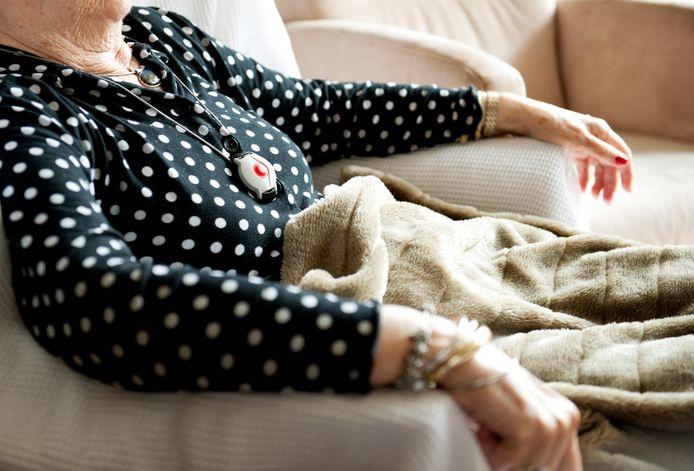 Een oudere dame draagt een alarmknop aan een halssnoer.