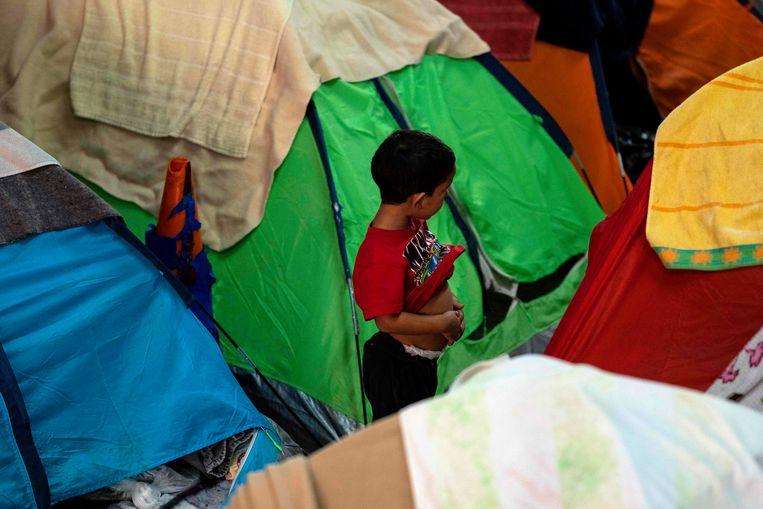 Een jongetje speelt in een tentenkamp van migranten bij Tijuana in Mexico.  Beeld AFP
