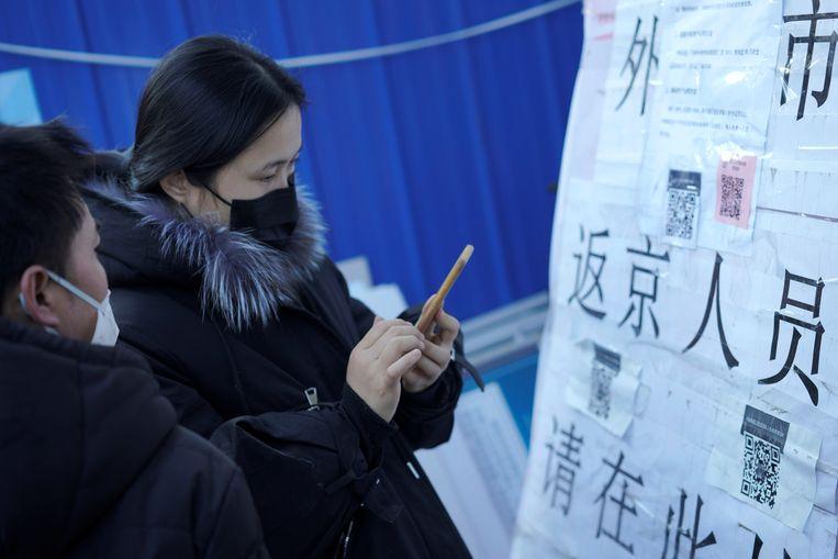 Mensen scannen een QR-code om hun risicoprofiel door te geven terwijl ze Beijing betreden. Beeld null