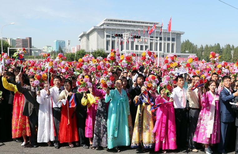 Noord-Koreanen zwaaien met vlaggen en boeketten tijdens de autoparade van de Koreaanse leiders.  Beeld AFP