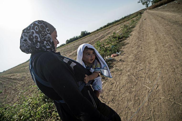 Een vluchteling loopt met haar baby naar de Kroatische grens. Beeld afp