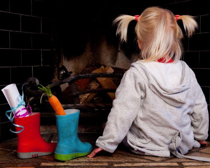 Een meisje zet haar schoen voor Sinterklaas bij de open haard, inclusief verlanglijstje.
