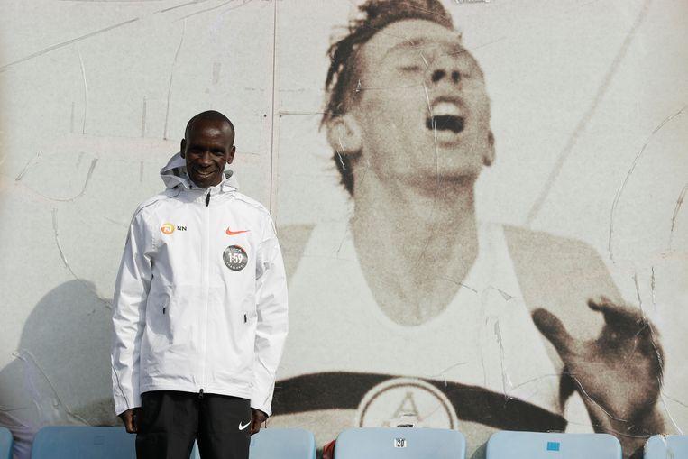 Eliud Kipchoge poseert bij een foto van  Roger Bannister, de Brit die in 1954 als eerste de Engelse mijl (ruim 1609 meter) onder de 4 minuten liep, destijds een onmogelijk geachte prestatie. Beeld AP
