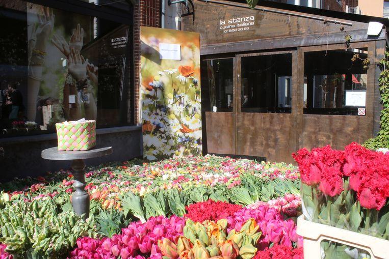 Warm bloementapijt klaagt het geweld van de voorbije weken aan. Het mandje met boodschappen in enveloppen te midden van de bloemen.