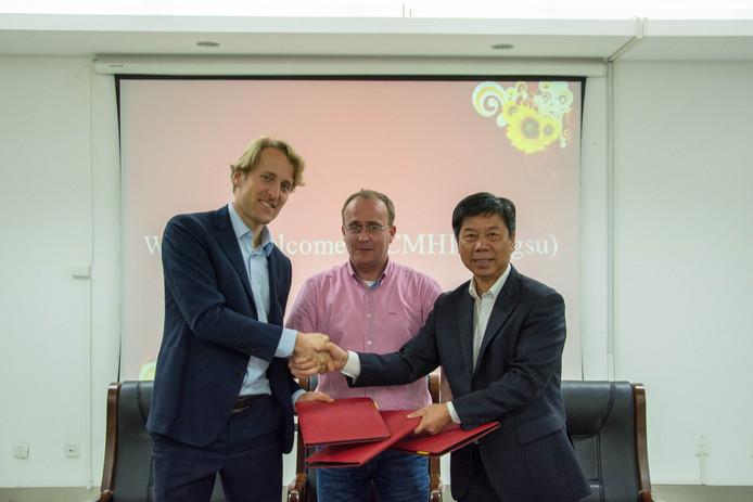 Het contract is getekend. Algemeen directeur Leon Overdulve van OOS International b.v. in het midden.