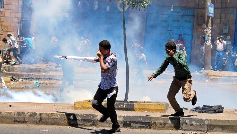 Burgers beschermen zich tegen traangas van de Houthi-rebellen in Taiz. Beeld afp