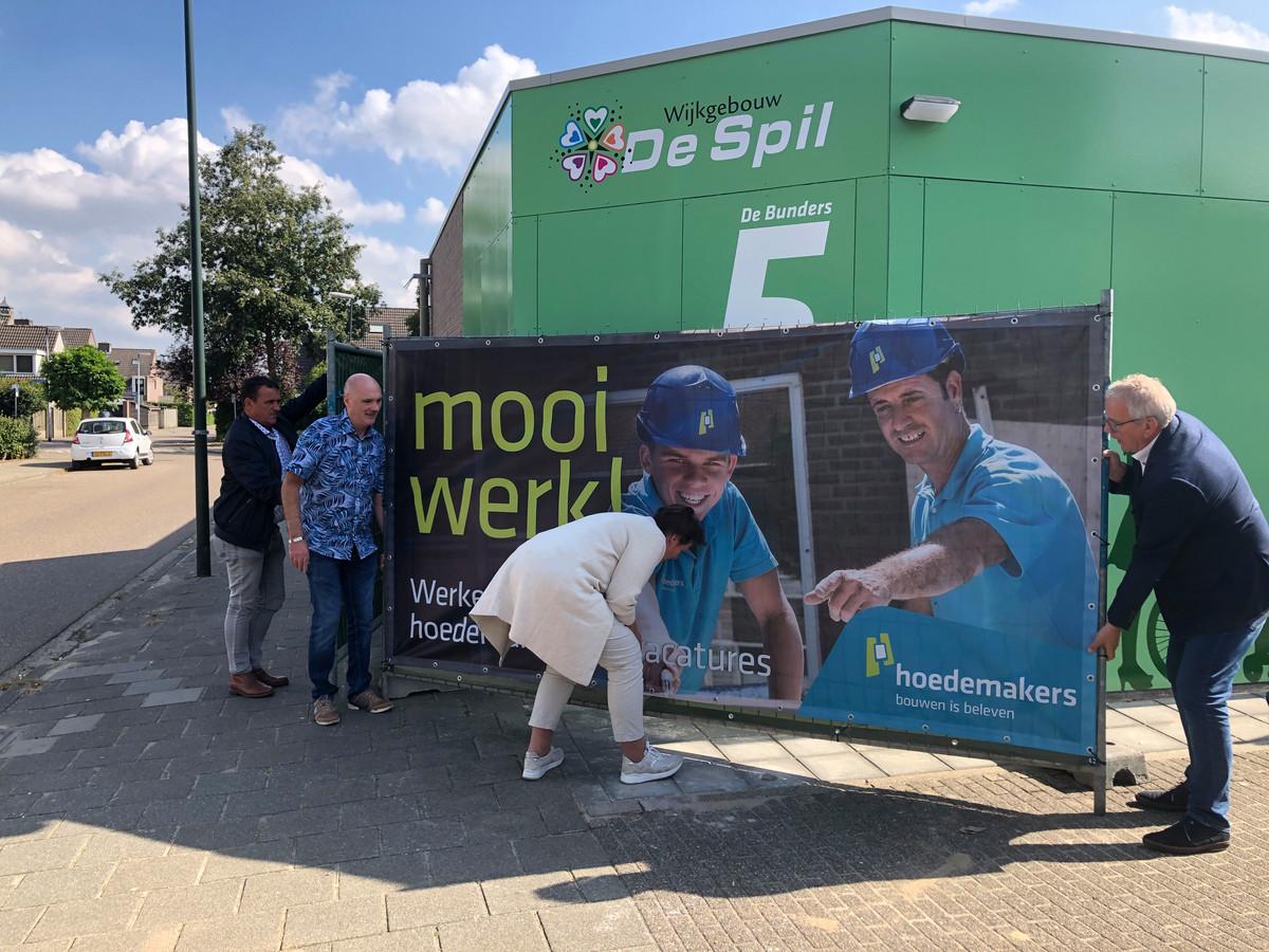 Wethouder Coby van der Pas (midden) tilt met voorzitter Hans van Zantvoort van de wijkvereniging en vrijwilliger/beheerder Peter Schepers het bouwhek weg. Daarmee is de Spil 2.0 geopend.