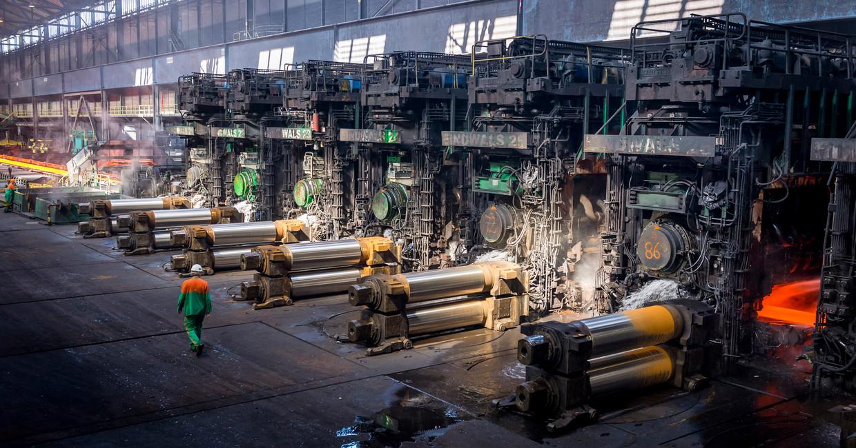 Plakken staal worden tot rollen uitgewalst bij Tata Steel in IJmuiden.