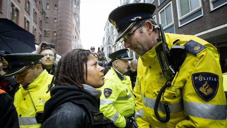 Een demonstrant in discussie met een politie agent tijdens de Sinterklaasintocht in Amsterdam. Beeld null