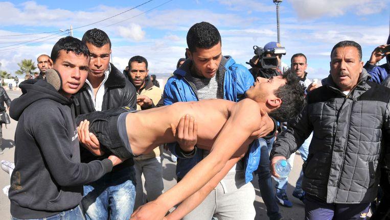 Een jonge Tunesiër die zelfmoord probeerde te plegen wordt door omstanders weggedragen voor medische hulp. Beeld afp