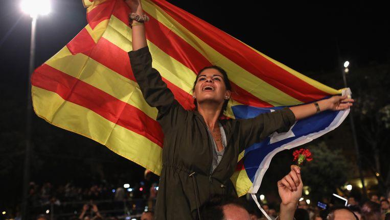 Een vrouw met de Catalaanse vlag wacht zondagavond in Barcelona op de uitslag van het referendum. Beeld getty