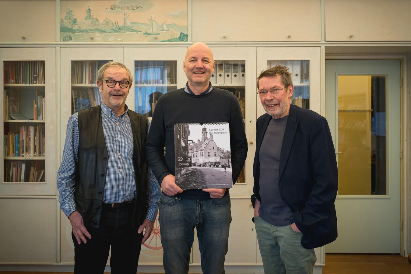 Aldert Onbelet (midden) met de nieuwe kalender van Wageningen.