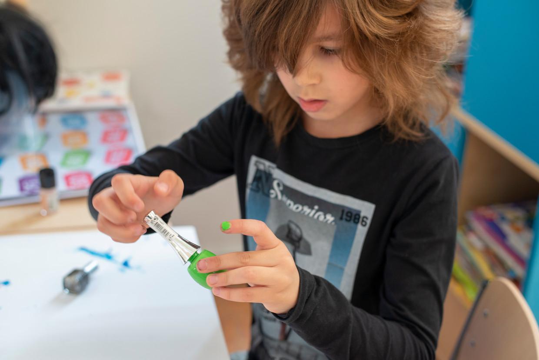 Een jongetje lakt zijn nagels in de verzorgingshoek van het klaslokaal.