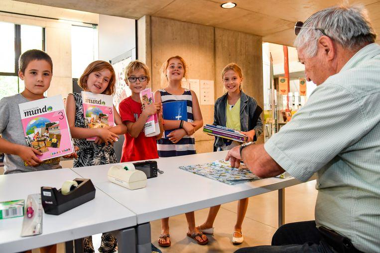 Een vrijwilliger kaft schoolboeken in de bib van Dendermonde, tot vreugde van de kinderen.