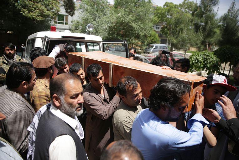 Na de bomaanslag van deze ochtend dragen enkele Afghanen de kist met daarin het lichaam van AFP-fotograaf Shah Marai weg.